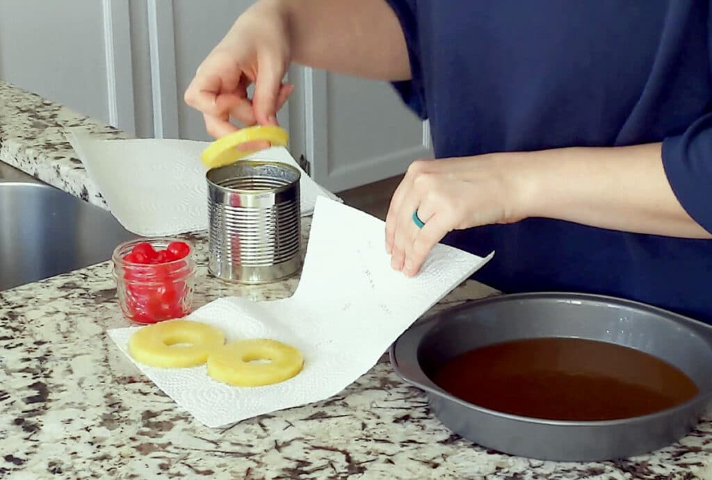 Marble counter top with cake pan to the right, filled with dark brown glaze on the bottom. A paper towel with two pineapple slices sits in the center with one hand holding the edge of the paper towel while the person's other hand grabs a pineapple ring from a can. Small jar of maraschino cherries sits to the left.
