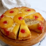 Top view of a pineapple upside down cake on a wood cake plate with three pieces of the cake sliced and the center of these three pieces rests on its side. A light brown towel is crumpled below the cake plate. White-grey marble background.