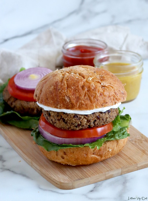 An assembled plant-based burger on whole grain bun with tomato, red onion, lettuce and white sauce, sits on light wood board with a bun less burger patty in the back. Behind the board sits a light brown towel with a small mason jar of ketchup and one of mustard to the back right.