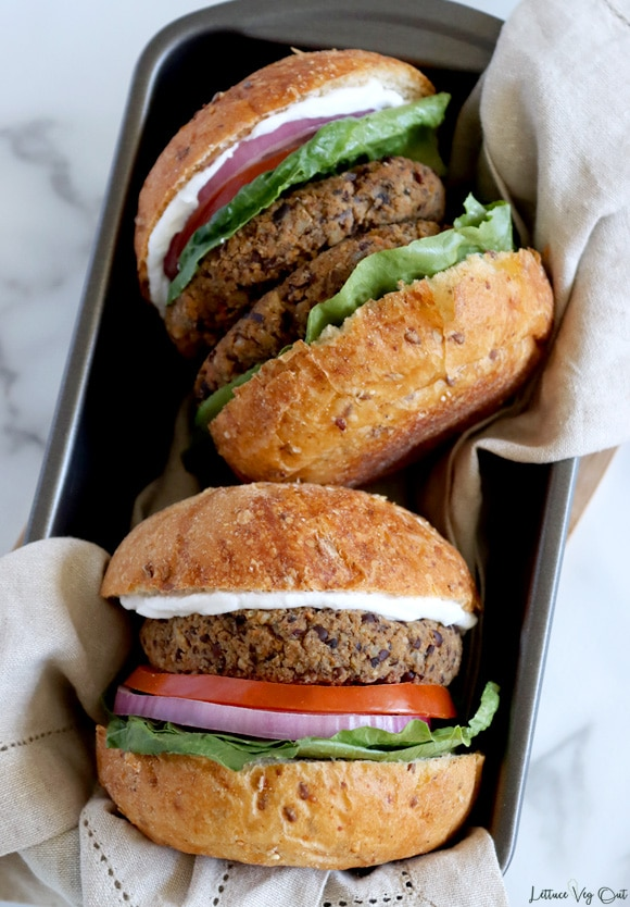 Top view of two assembled plant-based burgers resting in a loaf pan lined with a light brown towel. The top burger has two patties and the lower burger has one; both have white sauce, lettuce, tomato and red onion. White-grey marble background.