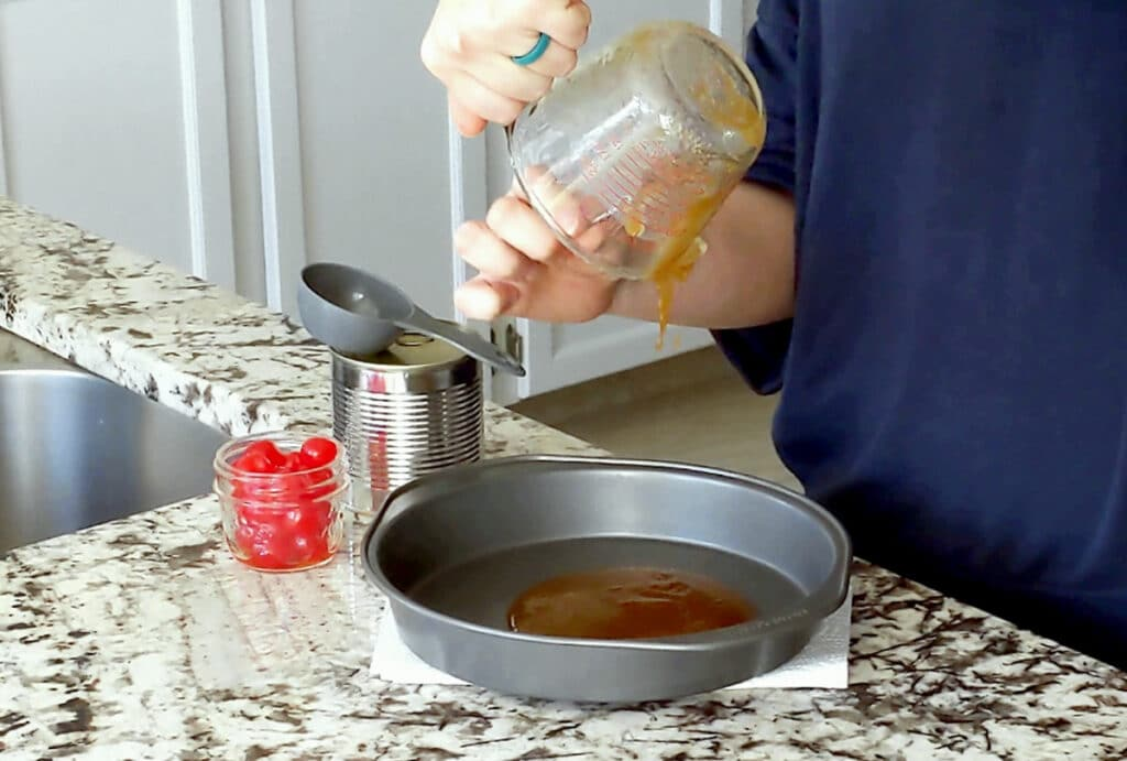Hands pour brown sugar glaze from a glass measuring cup into a round cake tin which sits on a marble counter. A can with grey measuring cup on top and small glass jar of maraschino cherries sits to the left.