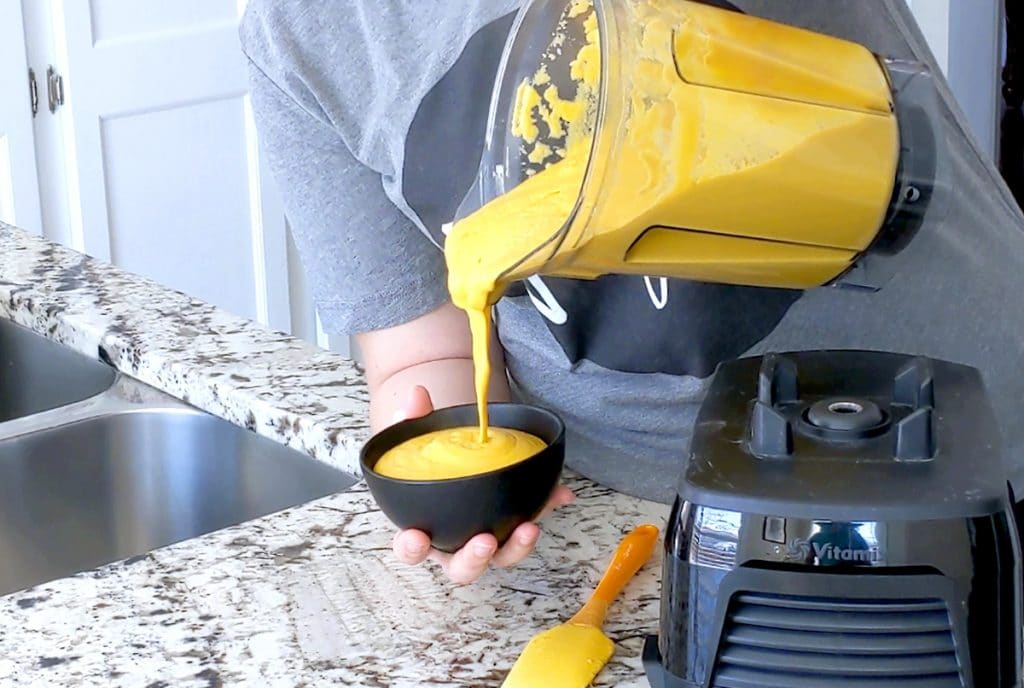 A person pours a blender filled with creamy orange sauce into a small black bowl that is held up by the person's other hand.