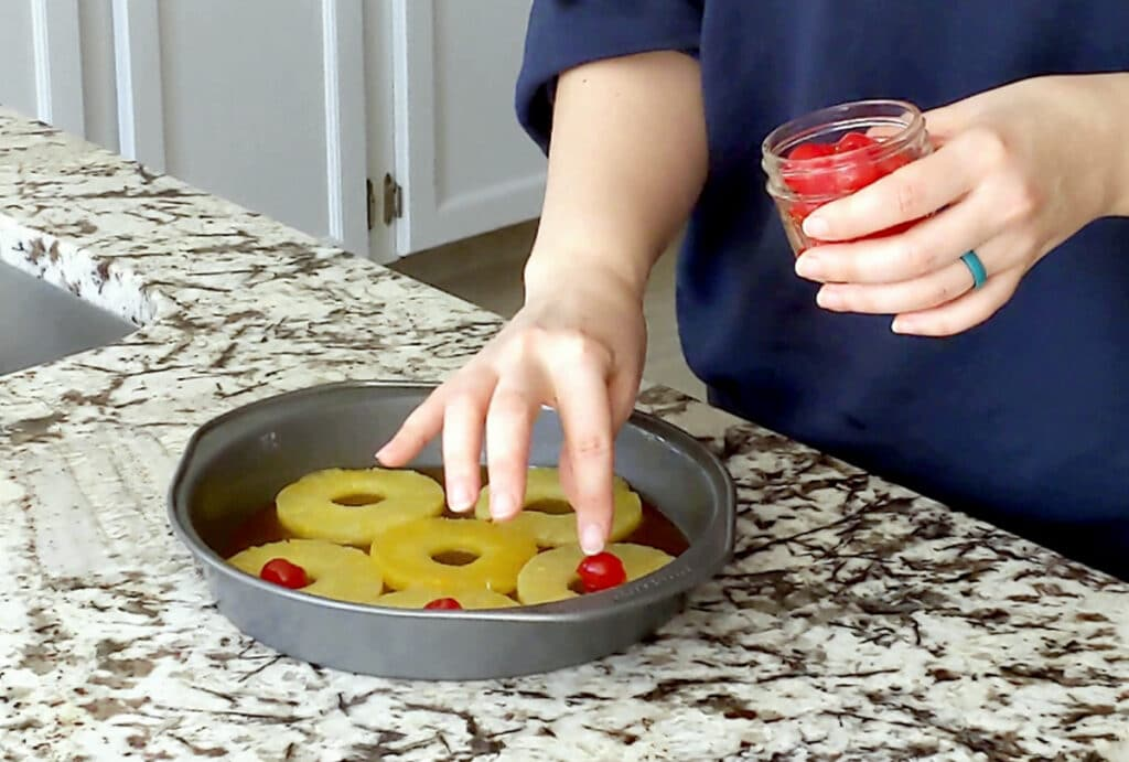 A hand places a maraschino cherry into the bottom of a cake pan that is lined with brown sugar glaze and pineapple slices. The person's other hand holds a small jar of maraschino cherries.