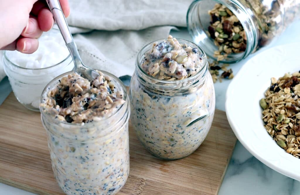 Two glass jars of Bircher muesli on wood board with small jar of yogurt behind. Bowl of muesli to the left, mostly cropped out, with a jar of muesli tipped on it's side to the top right of the image. A hand holding a spoon in the left jar of Bircher muesli appears mostly cropped in the top left corner.