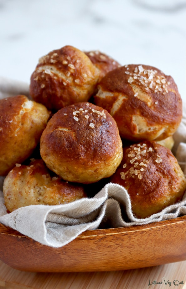 Stack of baked pretzel bites topped with coarse salt sitting in a wood bowl lined with light brown towel; the bowl sits on a light brown bowl.