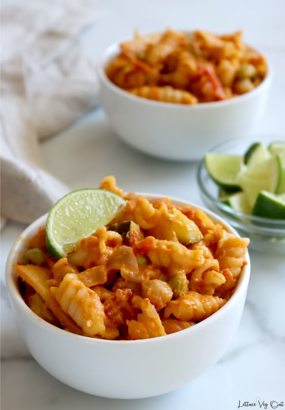 Small white bowl of creamy red curry pasta on rotini with chickpeas, edamame, zucchini and bamboo shoot pieces throughout. A lime wedge garnished the bowl on the back left edge. A second bowl, without a lime garnish, sits to the back left, slightly blurred out. A light brown towel is crumpled along the left edge of the image with a small glass bowl of lime pieces half cropped out, set between the bowls on the right side of the image.