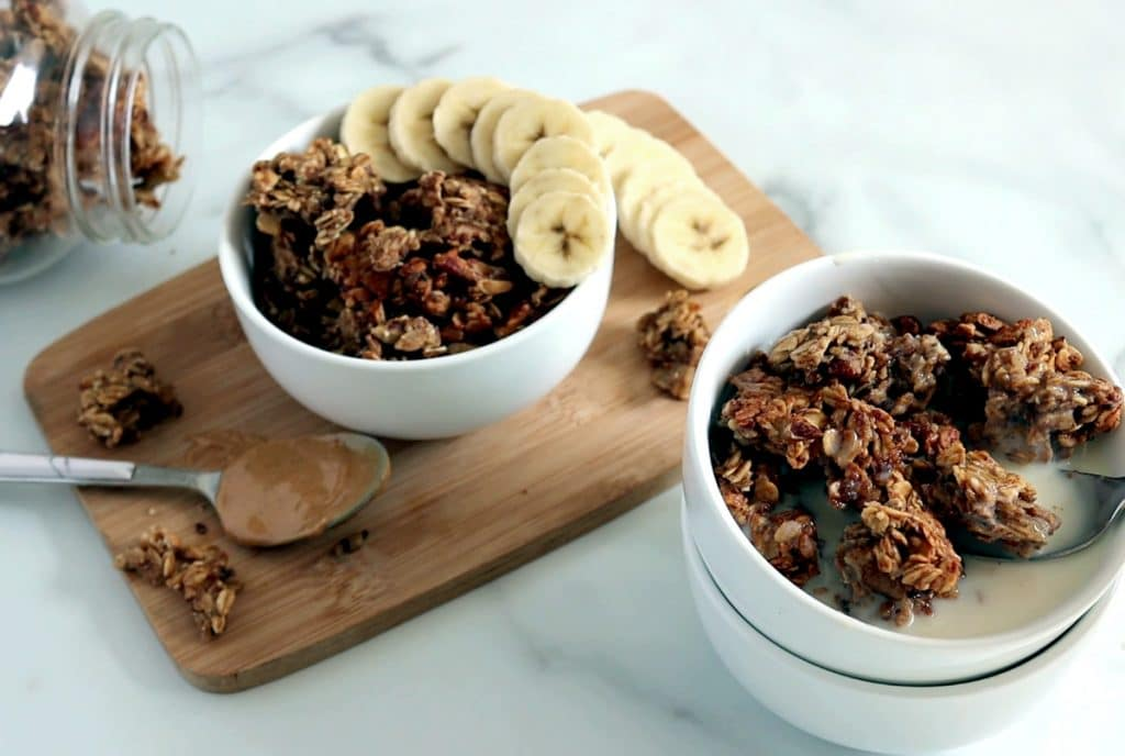 A stack of two white bowls filled with granola clusters and milk sits to the far right of the image. In the center is a small wood board topped with a bowl of granola with a row of banana slices across the top; on the board is a spoon of peanut butter, granola and banana slices. The top left corner sits a horizontal jar filled with granola.