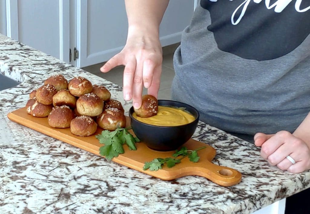 A narrow wood board topped with a pile of baked pretzel bites and a black bowl of cheese dip sits on a marble counter. A person stands behind the counter with one hand resting on the edge with the other hand holding a pretzel bite between two fingers and is dipping it into the cheese dip.