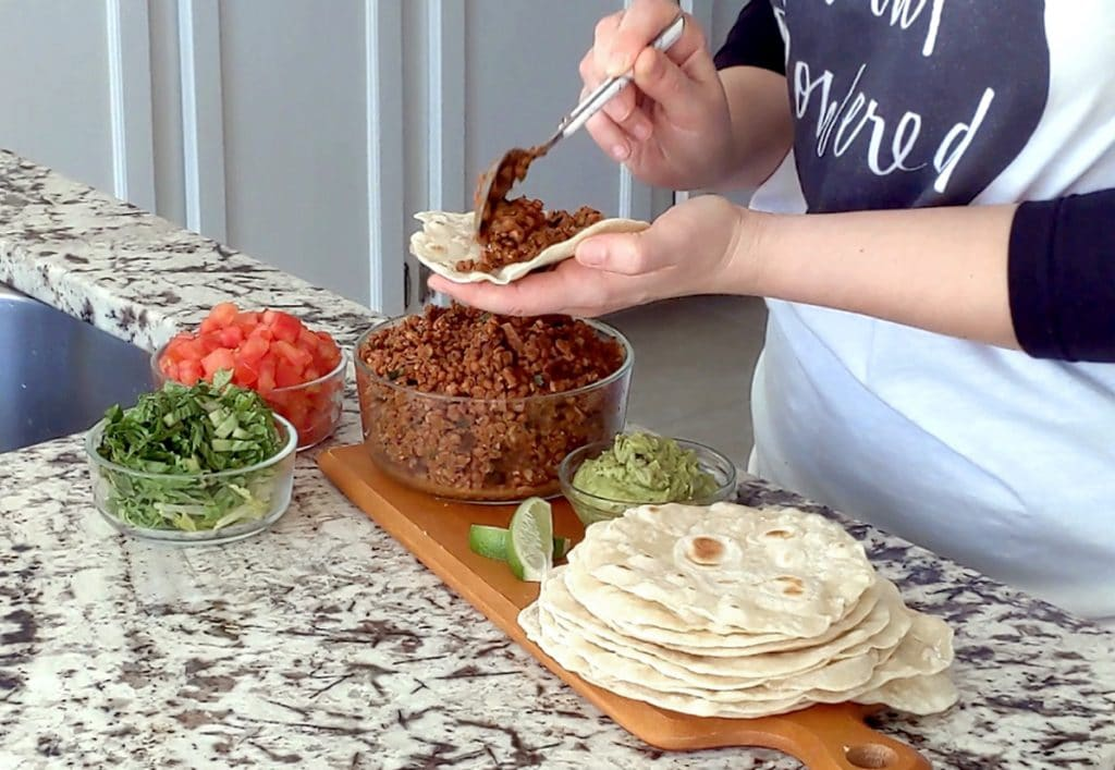 A person fills a flour tortilla with taco filling; one hand holds the tortilla flat while the other is scooping filling on top with a spoon. Below the hands is a long wood board topped with a stack of tortillas, a bowl of lentil taco filling, guacamole, lime wedges and two glass bowls of lettuce and tomato.