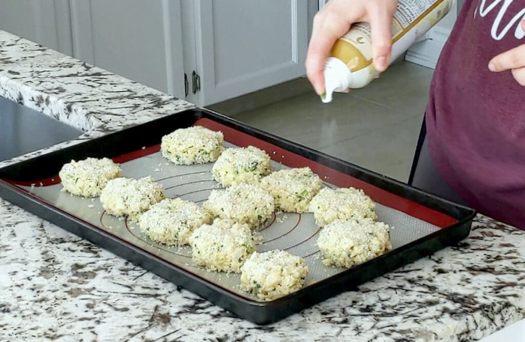 Hand holding a spray can of oil is spraying a tray of raw heart of palm crab cakes.