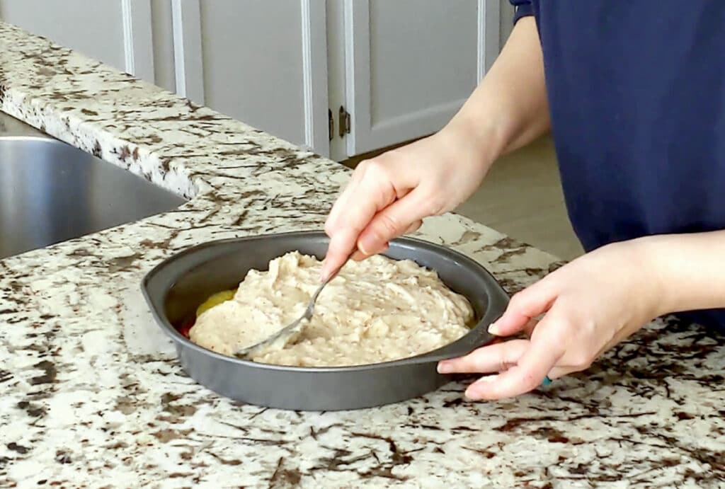 A person spreads cake batter in a round cake tin. One hand holds the right side of the cake pan while the other holds a spoon, spreading out the batter.