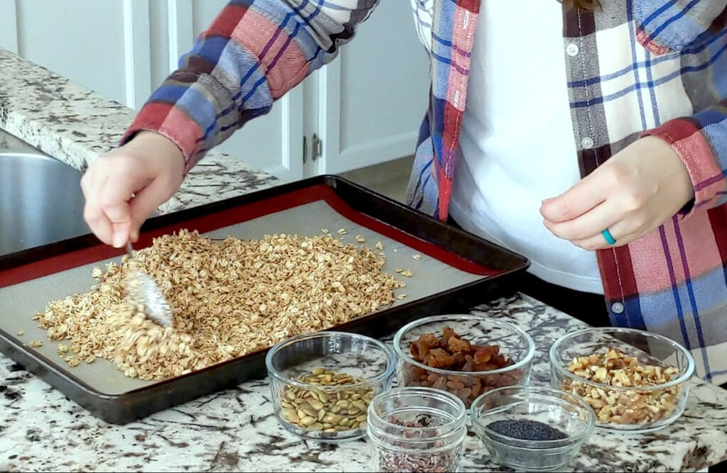Person holding spoon spreads out oats on a baking tray covered with parchment paper. Tray sits on marble counter to the left, with jars of muesli ingredients to the right (pumpkin seed, raisins, walnuts, poppy seeds and cacao nibs).