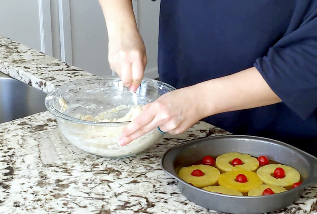 A person stirs a bowl of vanilla cake batter in a large glass mixing bowl. One hand holds the right side of the bowl while the other holds a spoon in the batter. A cake pan filled with pineapple rings and maraschino cherries sits on the marble countertop to the right.