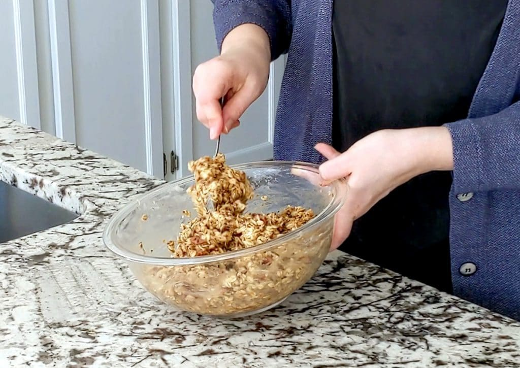 A person with fair skin stirs a granola mixture in a large glass bowl. One hand holds the bowl at a slight angle off the marble counter top while the other hand holds a spoon and is slightly blurred, in motion stirring.