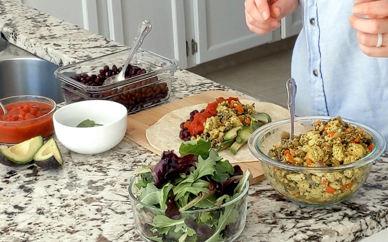 Countertop covered with ingredients to make breakfast burrito in glass bowls. In the center is a wood board with tortilla on it, filled with tofu scramble, avocado slices, black beans and salsa. A person stands behind the counter with hands held out in front (mostly cropped out).