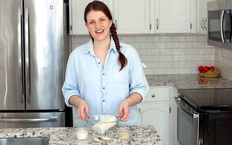 A woman with light skin and brown hair in a single braid stand behind a marble counter. She is smiling and wearing a light blue collared shirt with buttons and the sleeves rolled up.Her hands hold the edges of a large glass bowl with a piece of tofu in it. In front of the bowl are small glass dishes filled with different spices.