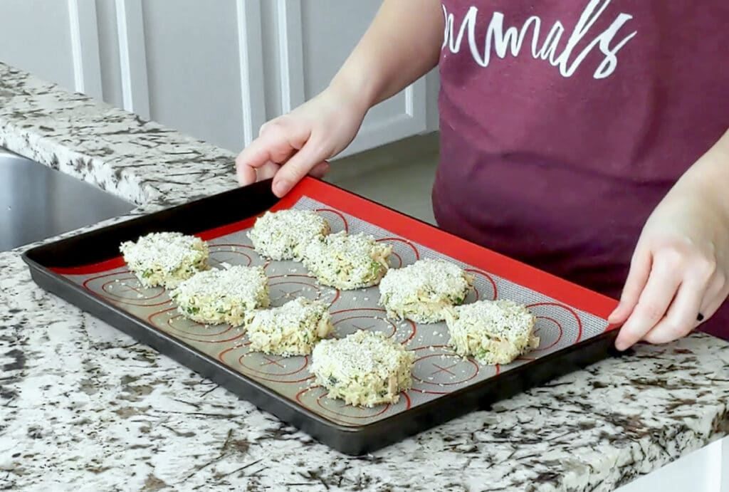 Hands hold either side of a baking tray topped with a silicone mat and breadcrumb-coated vegan crab cakes.