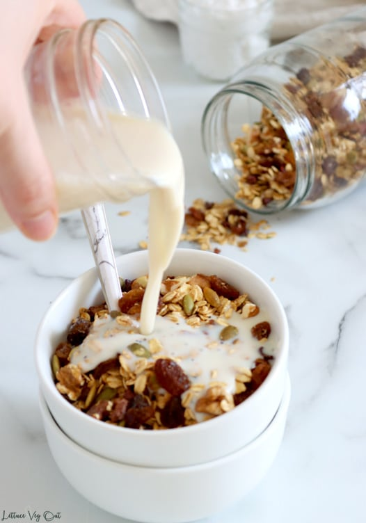 Hand pouring a jar of soy milk into a bowl of muesli with a spoon resting in it. A large jar of muesli, tipped on its side with some muesli spilling out, sits in the back right corner.