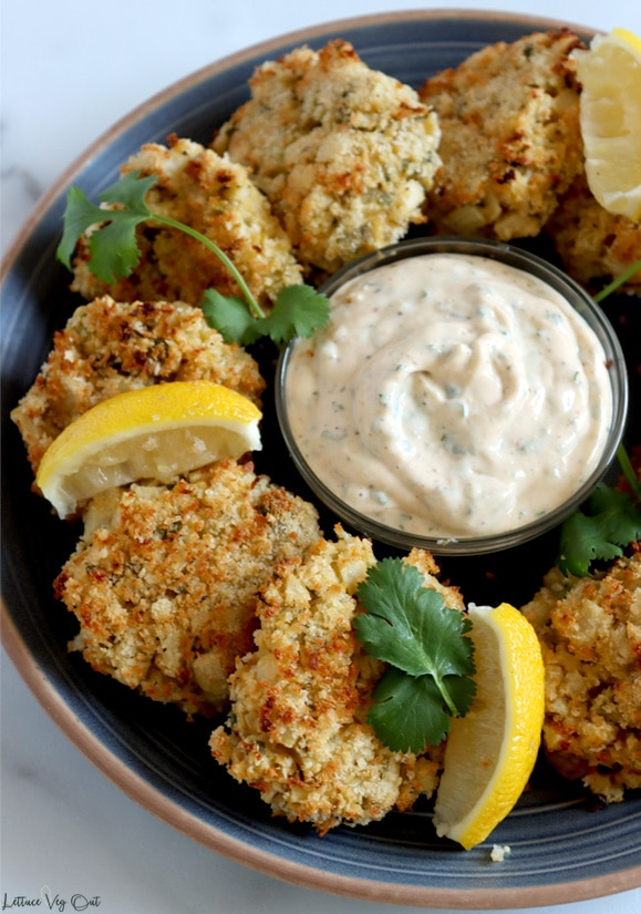 Top view of a blue plate with arrangement of crab cakes around the outer edge, surrounding a small glass bowl in the center that is filled with pale orange creamy dip. Lemon wedges and sprigs of parsley arranged around the crab cakes. Image is cropped so only 3/4 of plate showing, with white marble background.