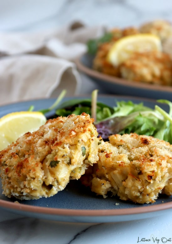 Close up of two heart of palm crab cakes with one resting at an angle over the other. They sit on a blue plate with salad greens and a lemon wedge behind them on the plate. A larger blue plate of crab cakes and lemon wedges sits blurred to the back right with a light brown towel blurred in the back left. White-grey marble background.