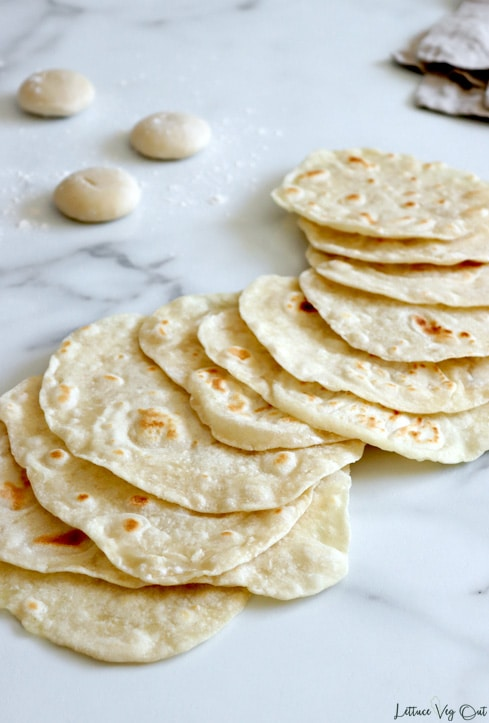 """Vegan tortillas curved in a slightly """"s"""" shape sit on a grey marble background. Three balls of tortilla dough sit in a sprinkle of flour in the top left corner."""