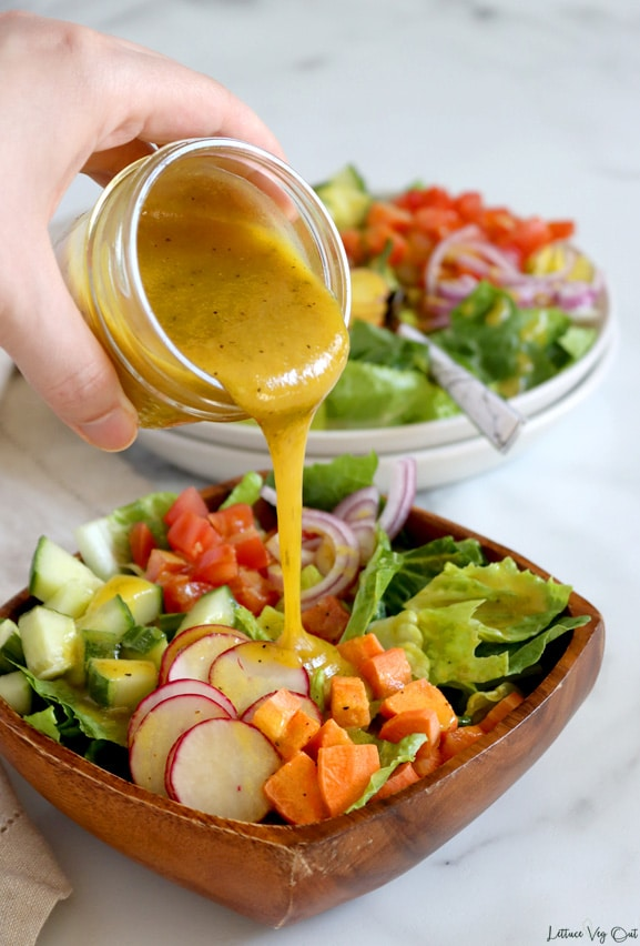Hand pouring a small mason jar filled with mustard salad dressing over a garden salad in square wood bowl. A double stack of round white plates, topped with garden salad (lettuce, radish, carrot, cucumber and tomato) sits blurred in the back. Light marble background.