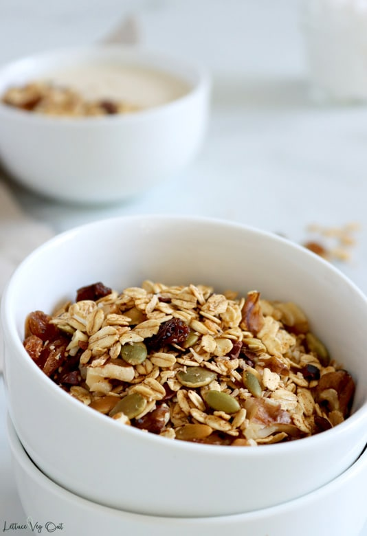 Close up of a double stack of small white bowls filled with muesli (oats, cacao nibs, raisins and pumpkin seeds visible). A blurred bowl of Bircher muesli sits blurred in the back left.