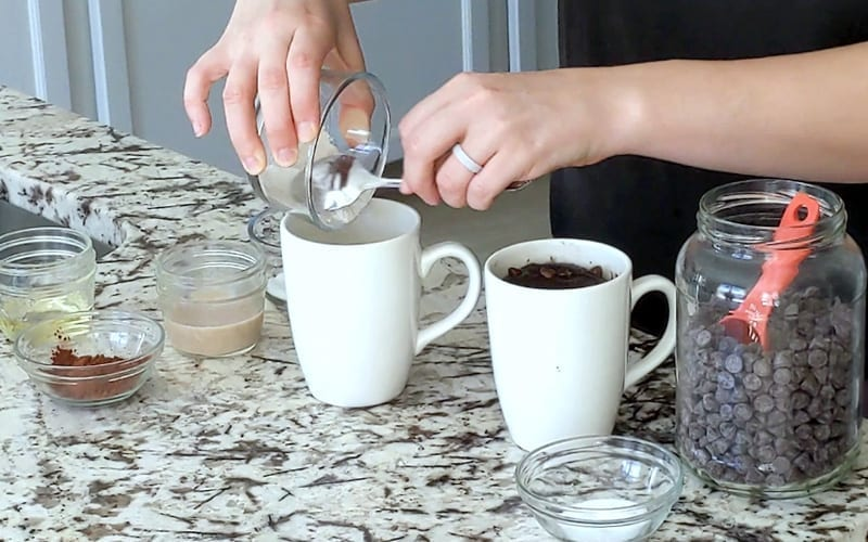 Hands scoop flour out of a small glass dish into a large white mug. Around the mug sit additional ingredients in small glass bowls including coco powder, milk, oil, sugar and a large jar of chocolate chips with a red spoon in it.