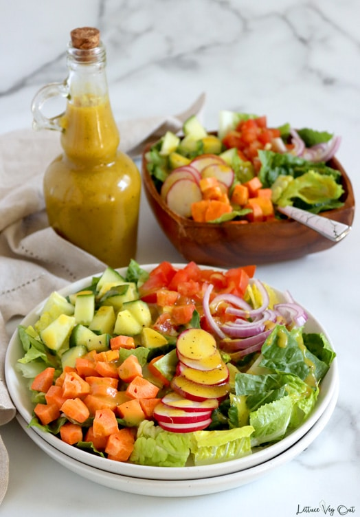 Double stack of white plates in front of image with square wood bowl behind; both filled with garden salad topped with mustard salad dressing. Tall, narrow jar of yellow salad dressing sits to the left, between the bowl and plate with a light brown towel along the left edge of the image. White-grey marble background.