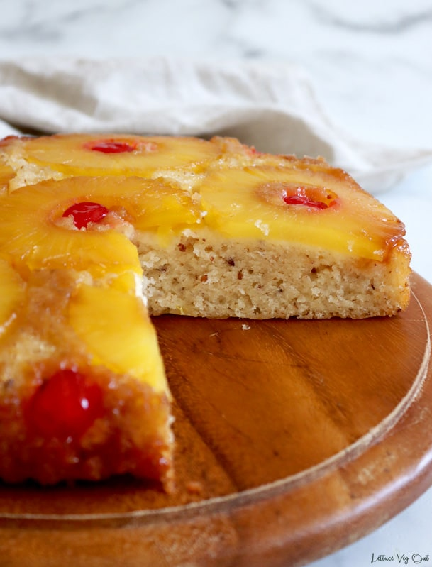 Front view of a round pineapple upside down cake with a quarter of the cake sliced out, showing inside texture of the cake. Light brown towel crumpled behind the cake board with a white-grey marble background. About a third of the cake is cropped out on the left side of the image.
