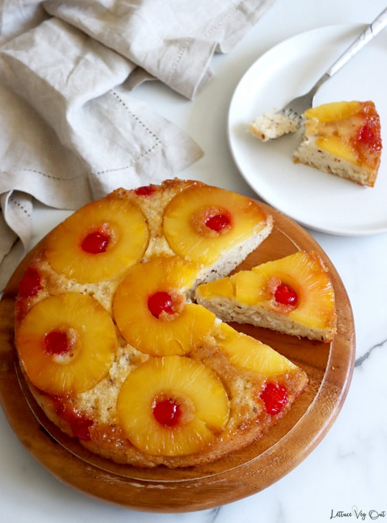 Top view of a pineapple upside down cake with a slice removed and second slice cut and centered in the gap created by the removed slice. Cake sits on a round wood cake board with a crumpled light brown towel to the back. A plate with a slice of cake and fork holding a bite of the cake sits in the back right corner.