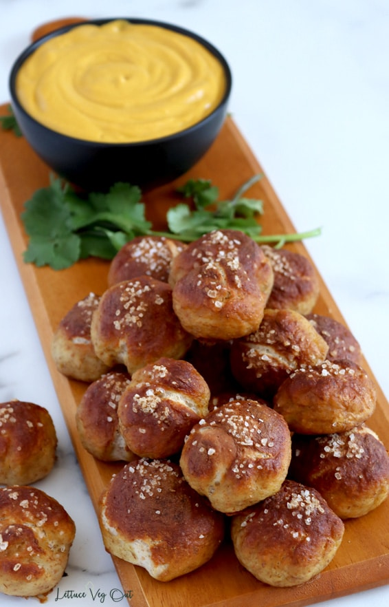 Top view of a long, narrow wood board with stack of soft pretzel bites piled at the front; two bites sit off the board to the left, on a white marble counter. At the back of the board there's a black bowl filled with beer cheese dip and pieces of cilantro sit around the bowl.