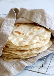 A stack of vegan tortillas sit wrapped in a light brown towel over top a metal wire cooling rack on a marble counter.