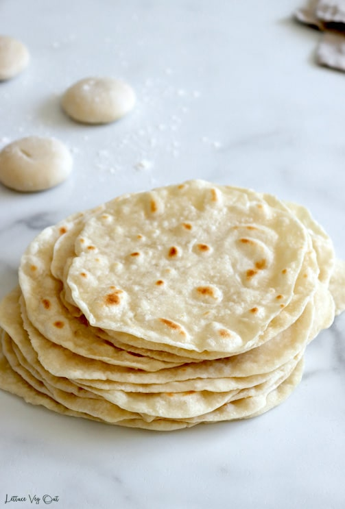 Stack of vegan tortilla wraps on a grey marble background with three balls of tortilla dough dusted with flour in the top left corner of the image. The corner of a folded brown towel sits blurred in the top right corner.