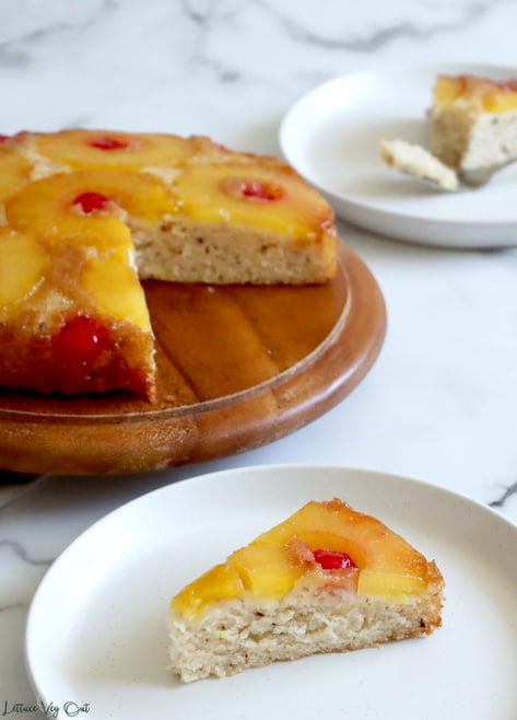 A slice of pineapple upside down cake sits on a white plate with the full pineapple cake on a wood board behind it. A quarter of the cake is missing, showing the inside texture. A second slice of the cake sits on a plate to the back right corner and is blurred out.