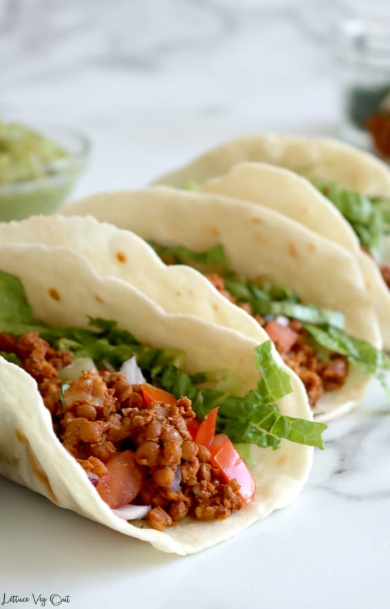 Row of three folded flour tortilla tacos filled with lentil walnut meat, tomato, red onion and lettuce; tacos become blurred toward the back and a glass bowl of guacamole sits to the back left.