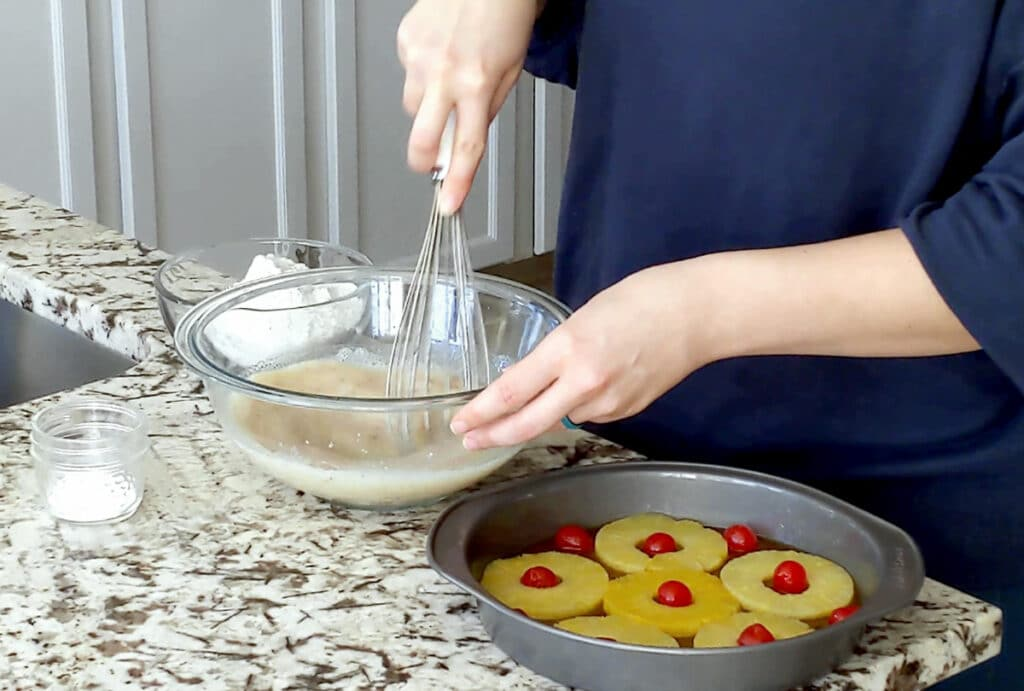 A person whisks liquid ingredients for a vanilla cake in a large glass mixing bowl. A cake pan filled with pineapple rings and maraschino cherries sits on the marble counter top to the right with a glass bowl of flour and small jar of baking powder sit to the rigth.