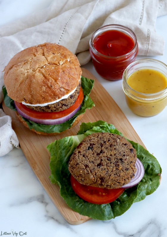 Top view of a small light wood board with an assembled burger to the back and a bun less burger patty at the front, resting on top of lettuce, tomato and red onion. Light brown towel wraps behind the wood board with two small mason jars of ketchup and mustard to the right.
