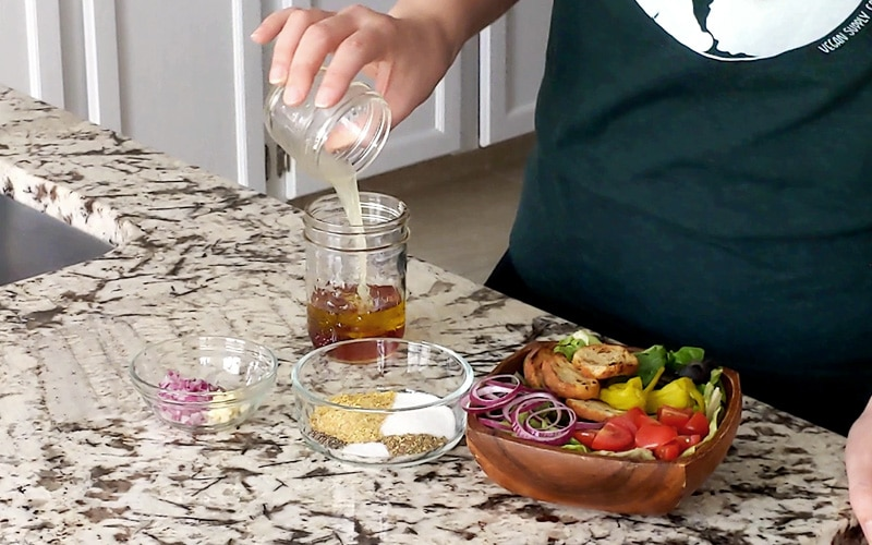 A hand pours lemon juice from a small glass jar into a larger jar filled with olive oil and red wine vinegar, to make salad dressing. Small bowl of minced garlic and red onion and another bowl of spices sits on the granite countertop. A square wood bowl of salad to the right of the salad dressing.