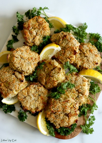 Top view of a square board topped with baked and breaded artichoke cakes and garnished with lots of parsley and lemon wedges with light grey background.