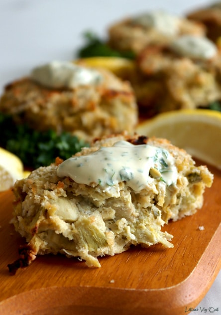 Breaded artichoke crab cake cut in half and topped with creamy dressing full of small green flakes sitting on long wood board with other whole crab cakes arranged behind it. Board garnished with parsley and lemon wedges. Grey background.
