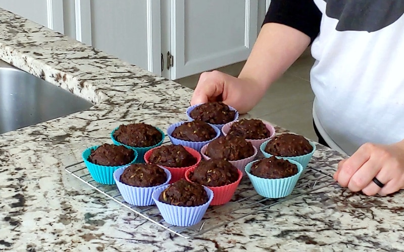 Square wire cooling rack topped with baked chocolate zucchini muffins that are in colorful silicone muffin wrappers. Cooling rack on a marble counter with a person, mostly cropped out, standing behind counter with hands resting either side of the cooling rack.
