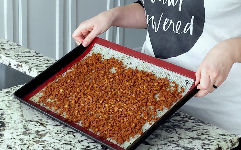 Hands holding up a baking tray topped with a silicone baking mat and cooked tofu bacon crumbles that are dark brown in color.