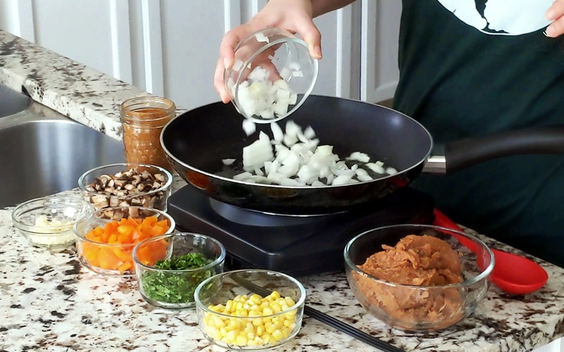 A hand pours a small glass jar of chopped white onion into a large black pan. The pan is surrounded by other small glass jars filled with quesadilla ingredients (refried beans, corn, cilantro, orange pepper, mushrooms, garlic and taco seasoning).
