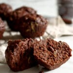 Chocolate zucchini muffins with chocolate chips, cut in half and sitting on white marble so you can see the inside of both halves. A cooling rack over a light brown towel and topped with whole muffins sits blurred in the background with a small jar of chocolate chips blurred in the back right corner.