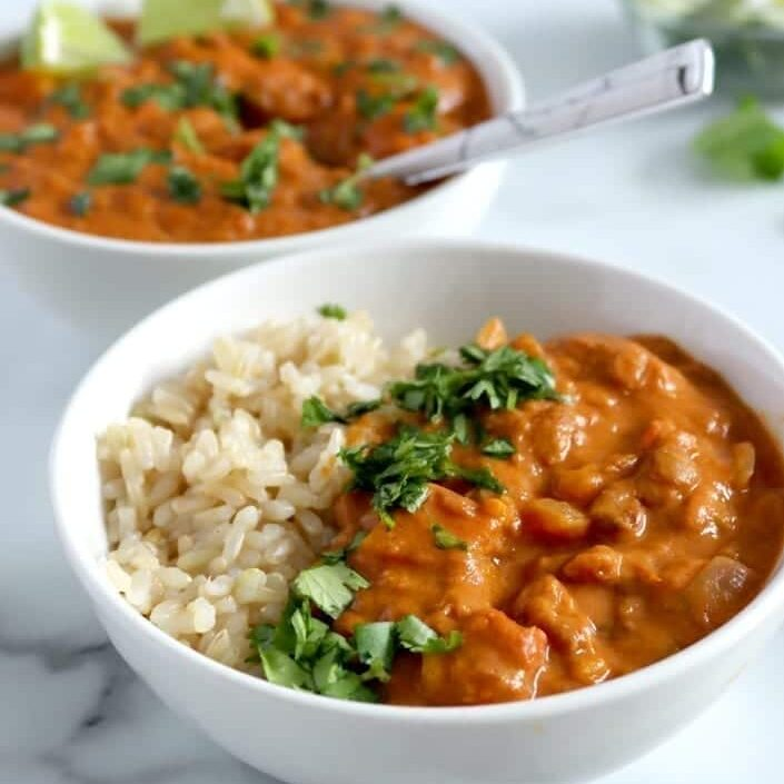 Two bowls of sweet potato lentil curry served from a slow cooker. Each bowl contains brown rice, curry and cilantro, while the second (back) bowl also contains two lime wedges