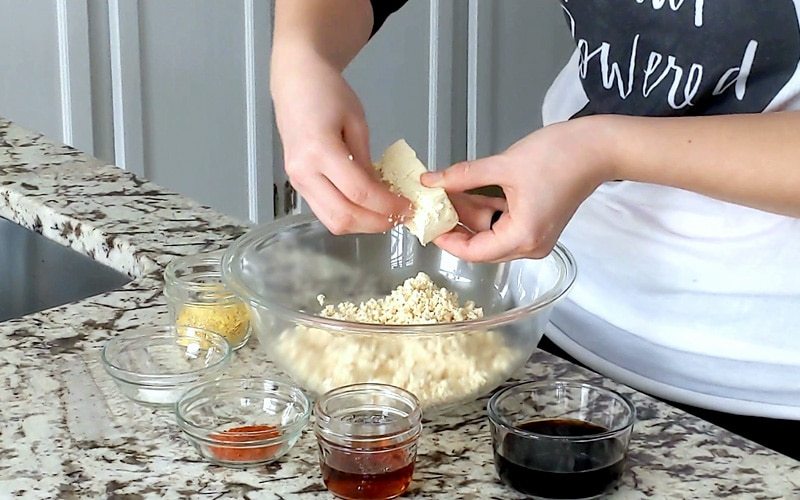 Hands hold a small piece of tofu over a bowl of crumbled tofu that is broken into very small pieces. Small glass dishes with ingredients sit on the marble counter around the large mixing bowl full of tofu.