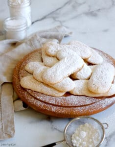 Pile of ladyfinger cookies, topped with sprinkled icing sugar, on a round wood board with white-grey marble background. A small metal sifter with icing sugar sits in front of the board and there's a light brown towel to the left with two small jars of white ingredients blurred in the back left corner.