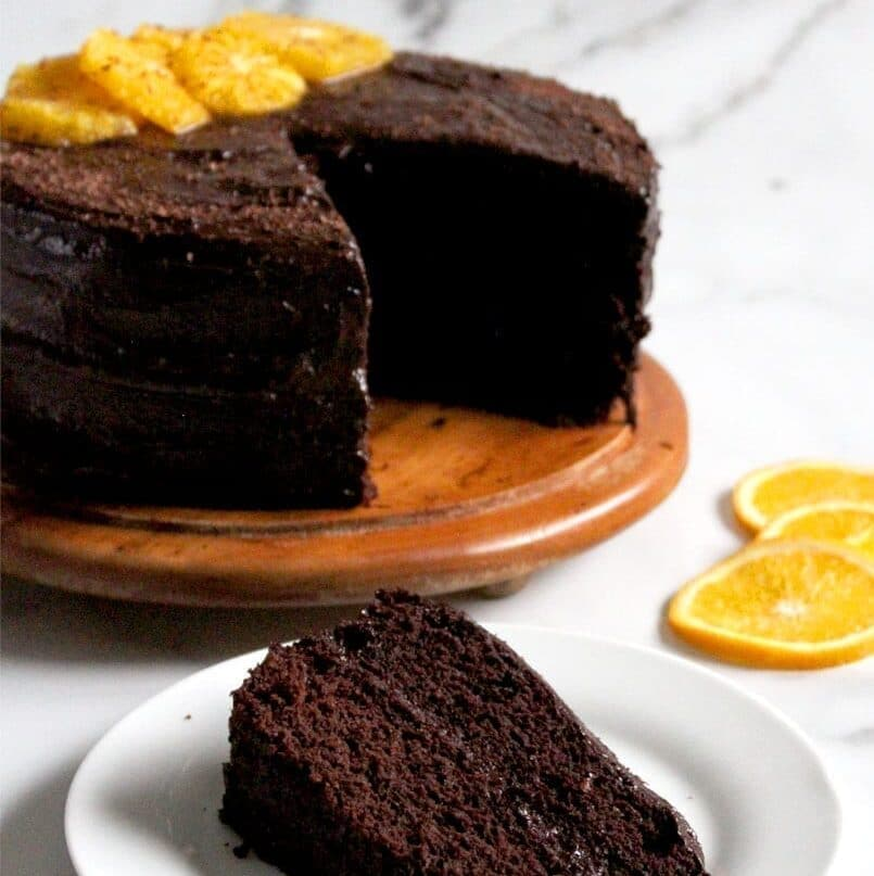 Vegan chocolate orange cake recipe with full cake in background and individual slice of dairy free, eggless cake in foreground