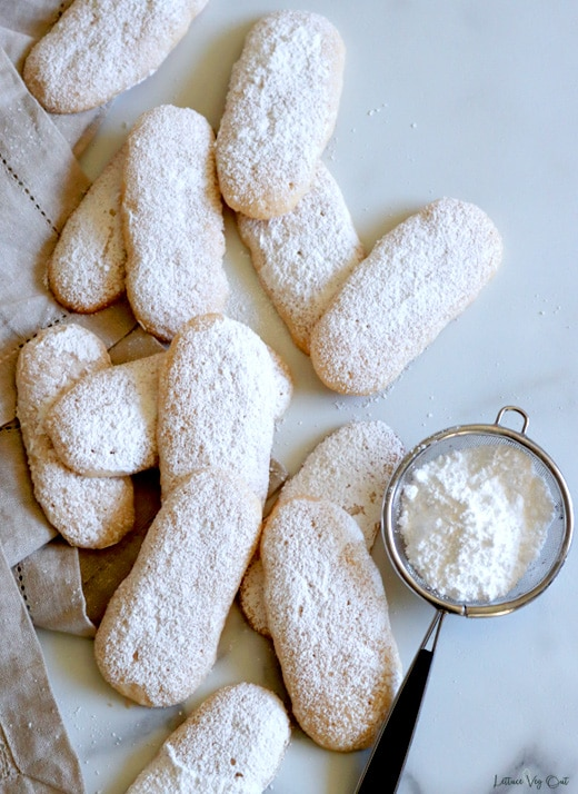 Top view of a pile of ladyfinger biscuits, topped with icing sugar, sitting on white-grey marble. A light brown towel is folded along the left edge and a small metal sifter filled with icing sugar sits to the right.